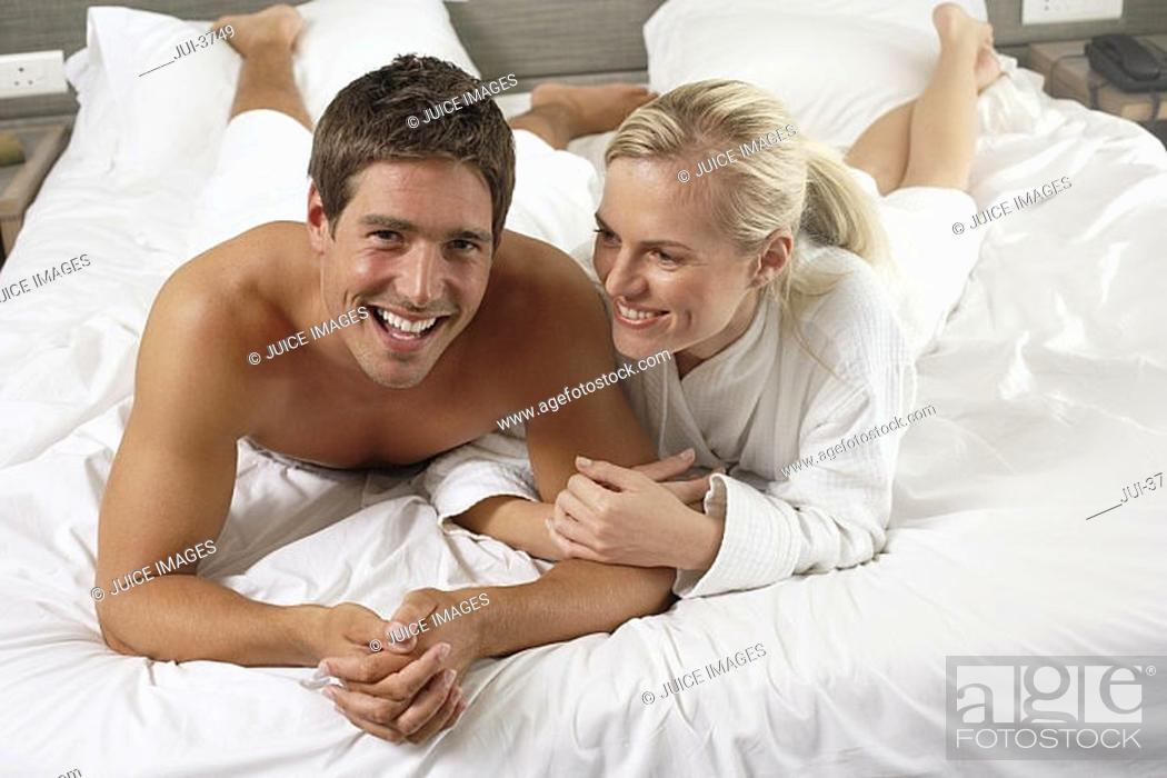 Stock Photo: Affectionate couple lying on hotel bed, smiling, front view, portrait.