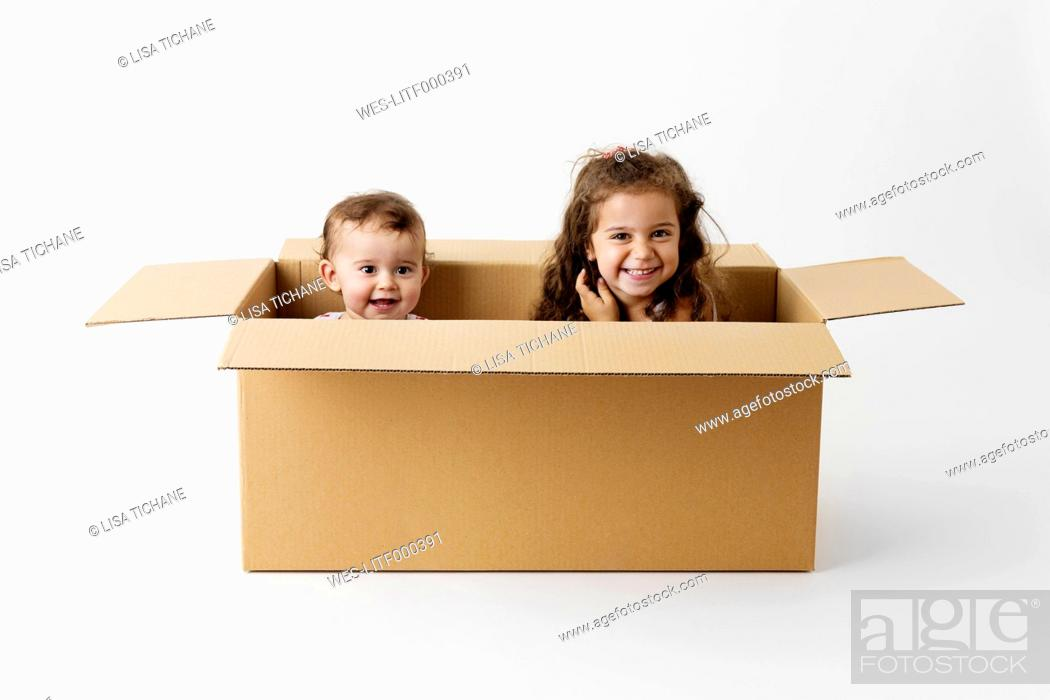 Stock Photo: Two happy little children together in a cardboard box.