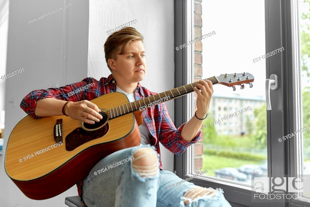 Imagen: young man playing guitar sitting on windowsill.
