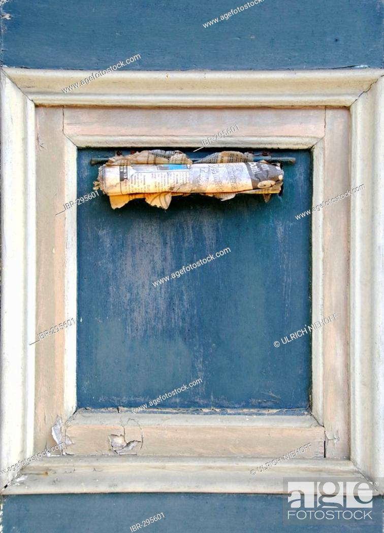 Stock Photo: Old newspaper in a letter slot of a frontdoor.