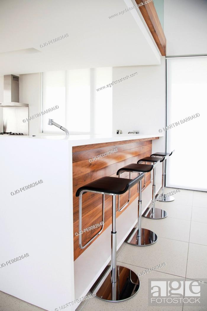 Stock Photo: Stools at counter of modern kitchen.