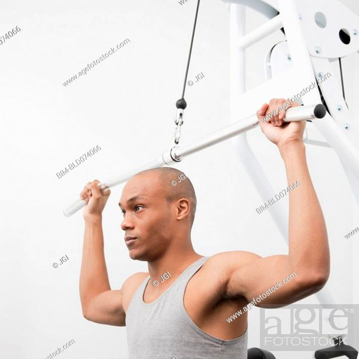Stock Photo: African man using weight machine in health club.
