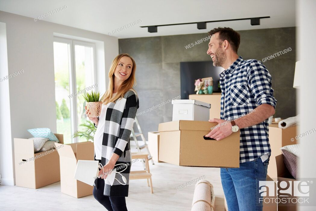 Stock Photo: Happy couple moving house carrying cardboard box and plant.