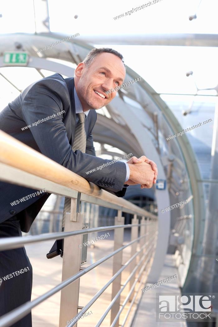 Stock Photo: Germany, Leipzig, Businessman leaning on railing, smiling.