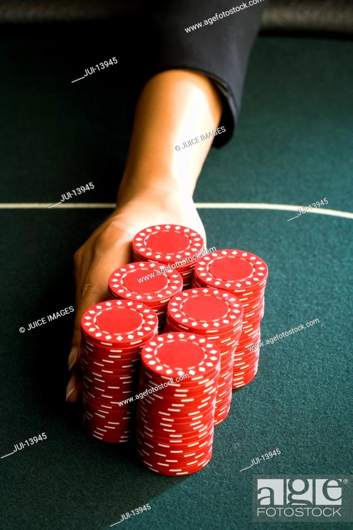 Stock Photo: Woman pushing gambling chips onto table, close-up of hand.