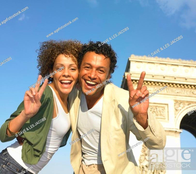 Stock Photo: Couple making peace signs next to stone arch in Paris.