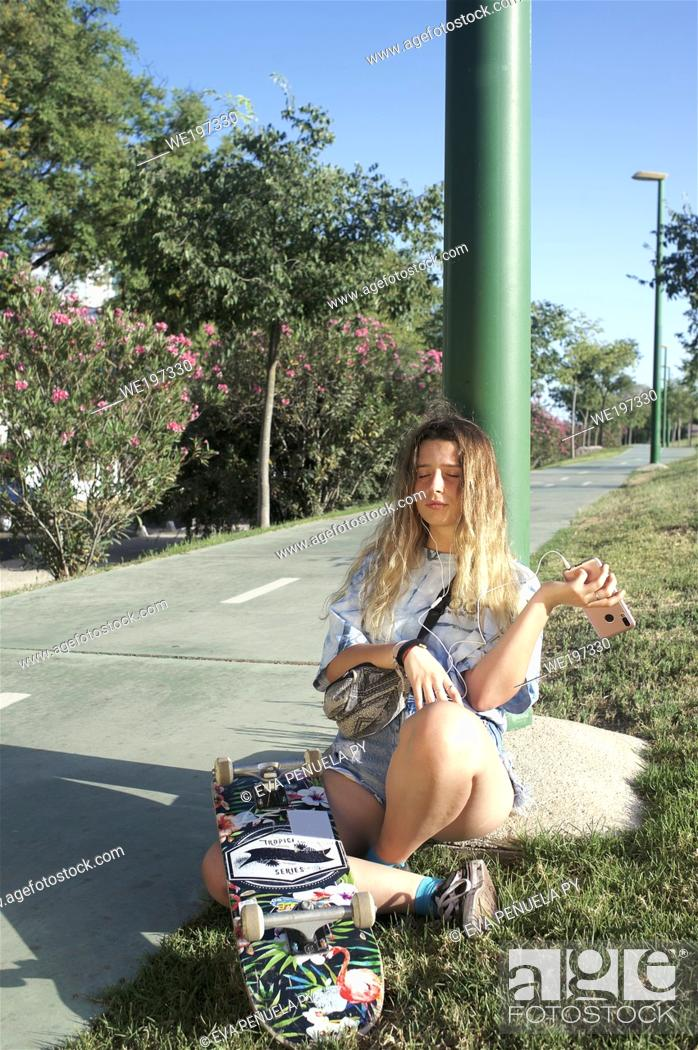 Stock Photo: Young girl with long blond hair practicing skate on the bike path on a summer afternoon in Seville.