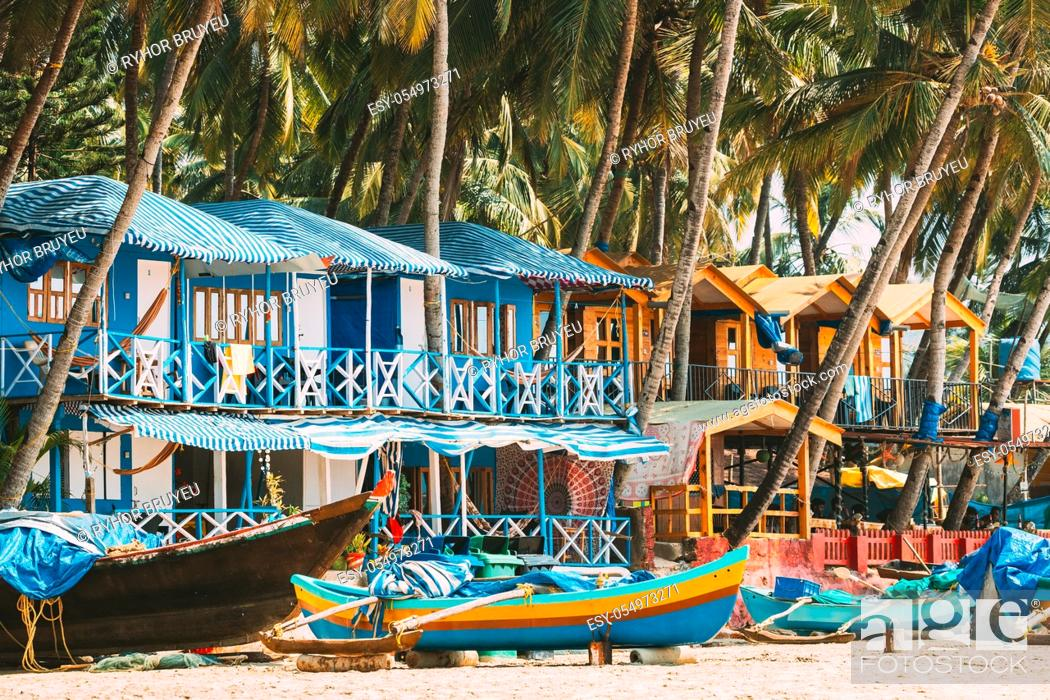 Stock Photo: Canacona, Goa, India. Fishing Boat And Famous Painted Guest Houses On Palolem Beach Against Background Of Tall Palm Trees In Sunny Day.