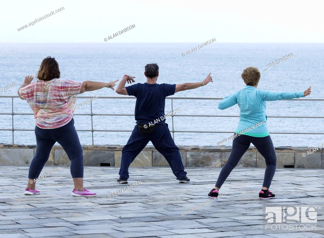 Stock Photo: Mature man and two mature women practicing tai chi overlooking the Atlantic Ocean in Las Palmas, the capital of Gran Canaria, Canary Islands, Spain.