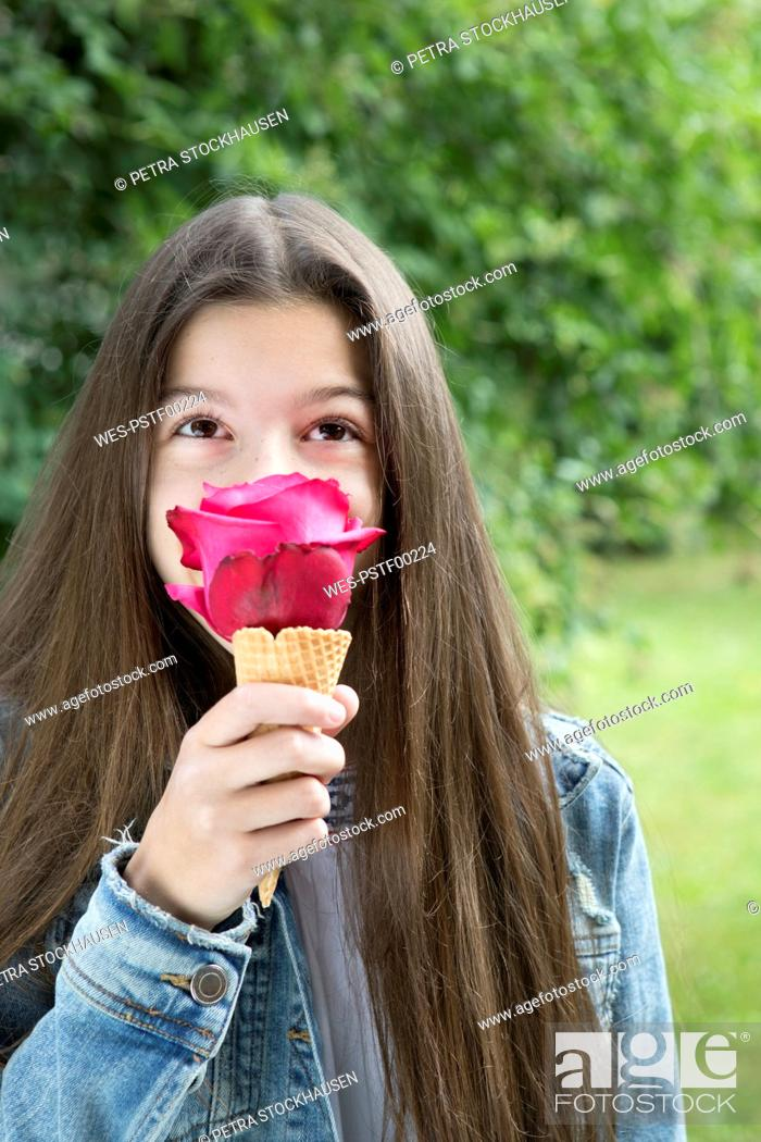 Stock Photo: Girl smelling pink rose blossom in ice cream cone.