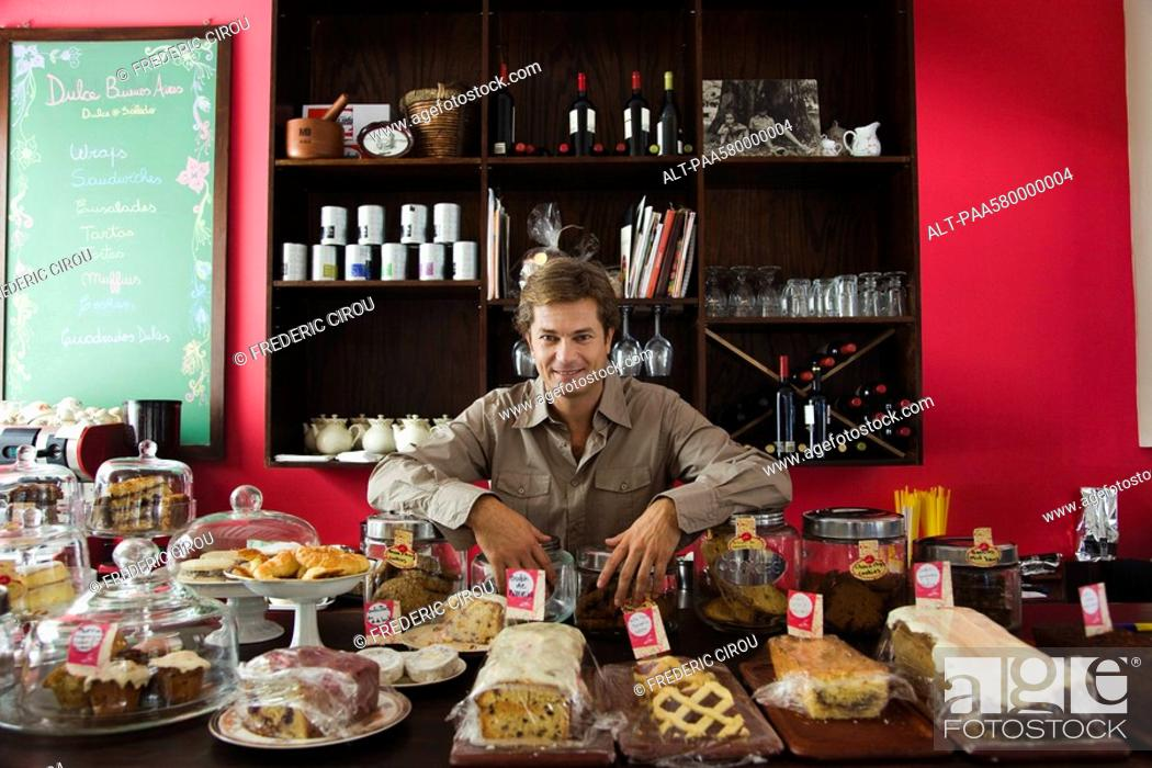 Stock Photo: Cafe owner, assorted pastries and baked goods on counter.