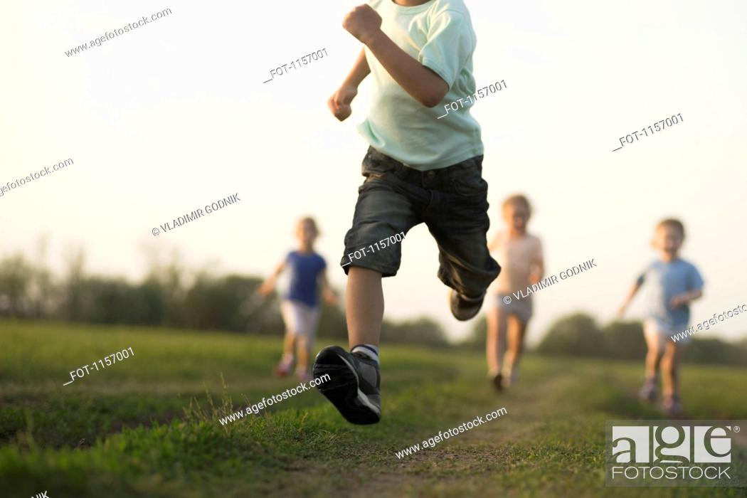 Stock Photo: Low view of a boy running in a field with other children behind.