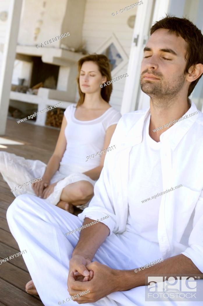 Stock Photo: Young couple in yoga attitude, outdoors.