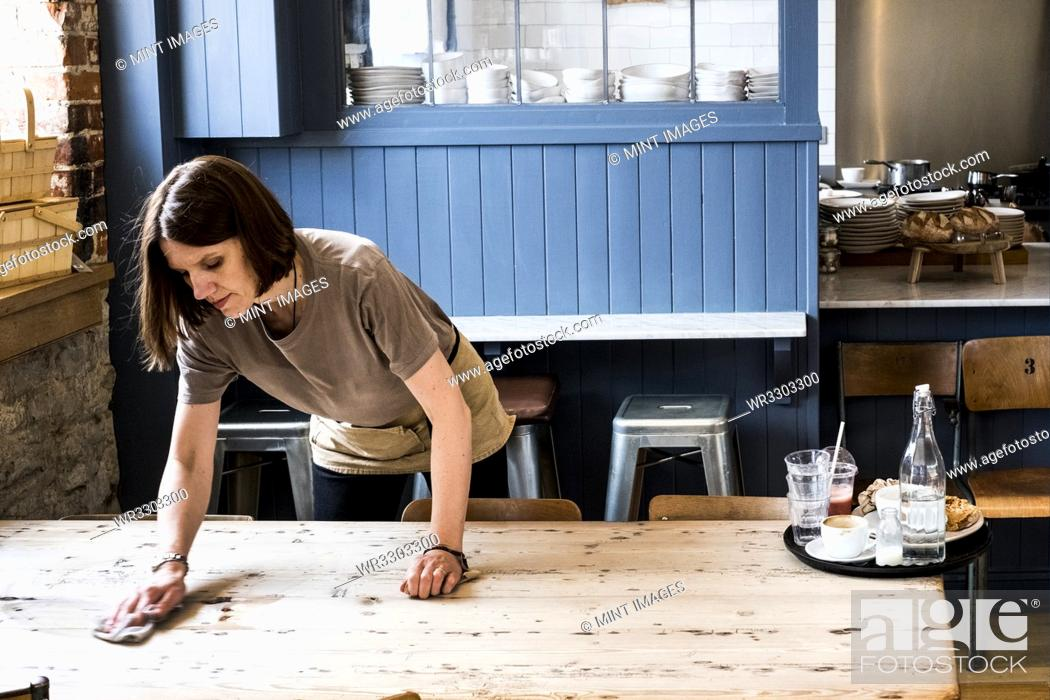 Stock Photo: A female waitress clearing a table and wiping it in a cafe.