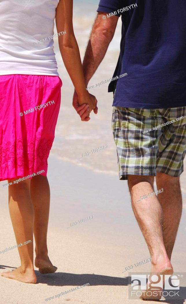 Stock Photo: Couple holding hands, walking on beach.