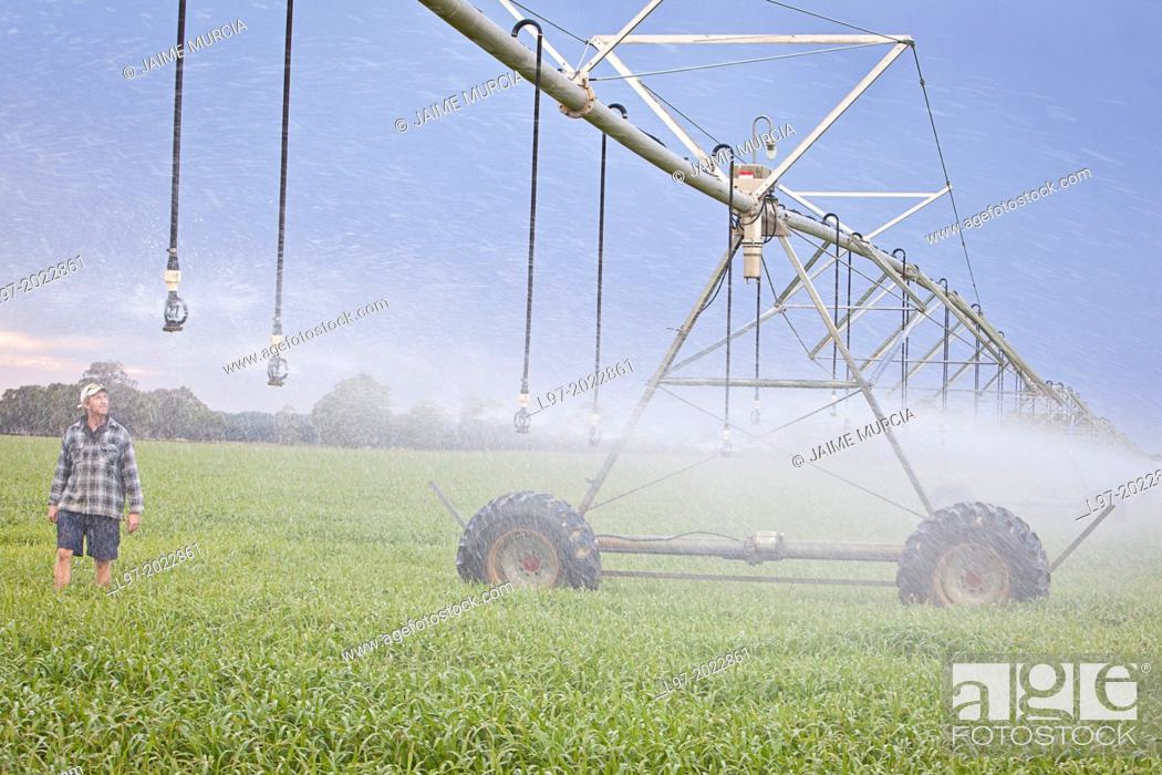 Stock Photo: A farmer inspects his center pivot irrigation system, Victoria Australia.