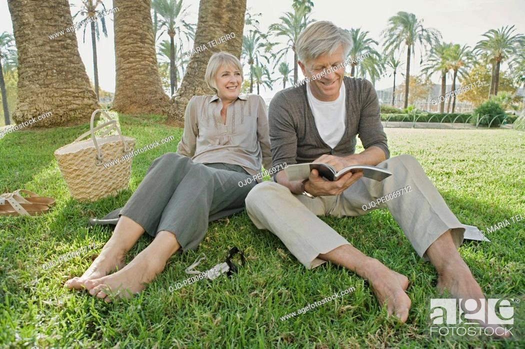 Stock Photo: Barefoot man and woman relaxing on grass.