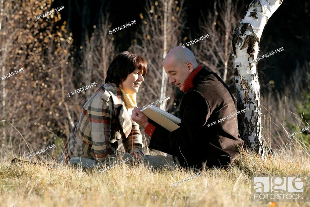 Stock Photo: Man and woman sitting in front of a wood, reading in a book.
