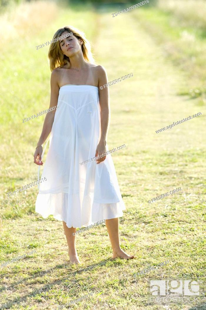 Stock Photo: Young woman standing in field, eyes closed, full length.