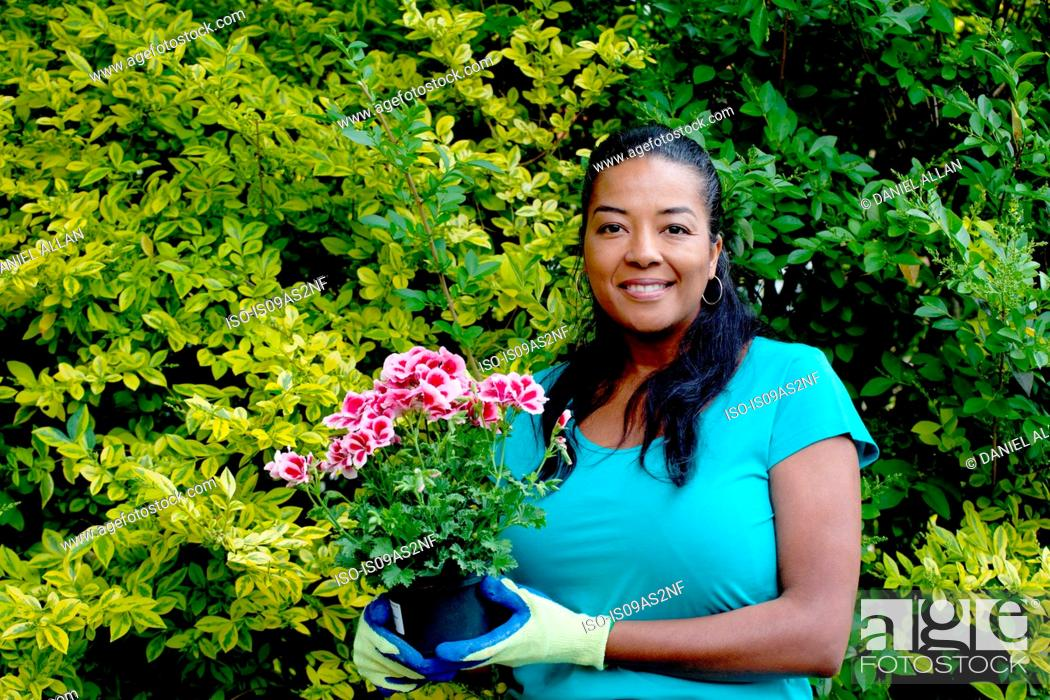 Stock Photo: Portrait of mature woman with flowering pot plant in garden.