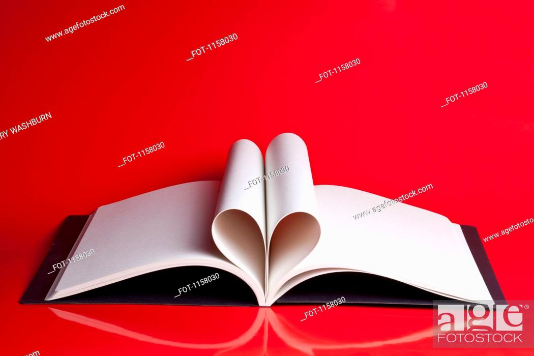 Stock Photo: An open hardcover book with pages folded to look like a heart.