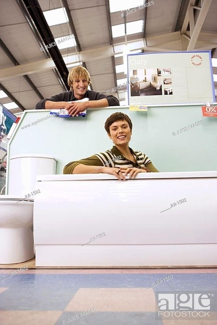 Stock Photo: Couple shopping in home furnishings store, woman sitting in bathtub, smiling, portrait.