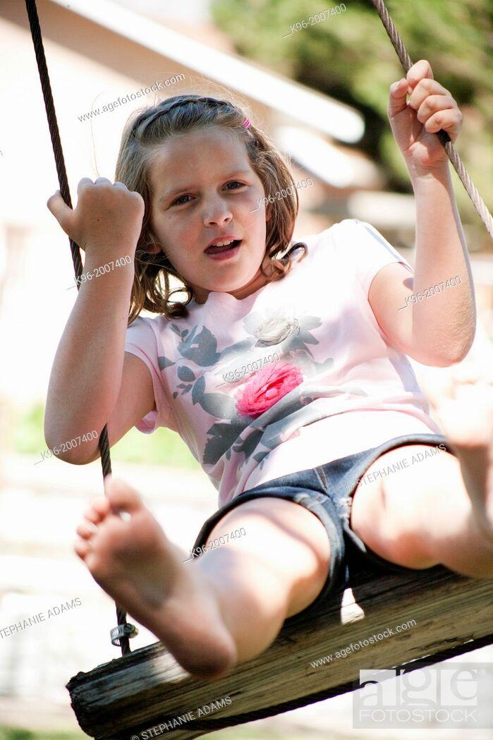 Stock Photo: young girl swinging.