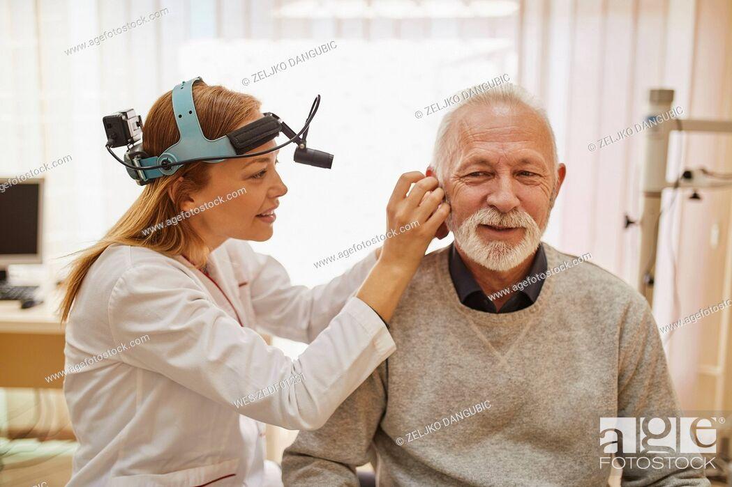 Stock Photo: ENT physician examining ear of a senior man.