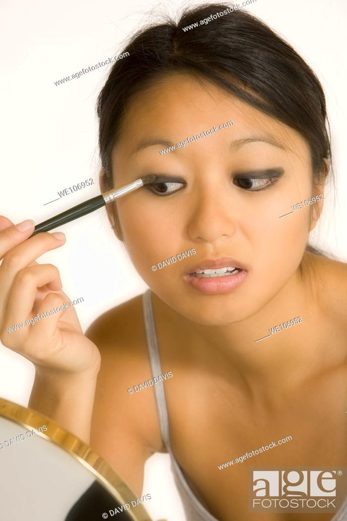 Stock Photo: Asian woman applying eye shadow.