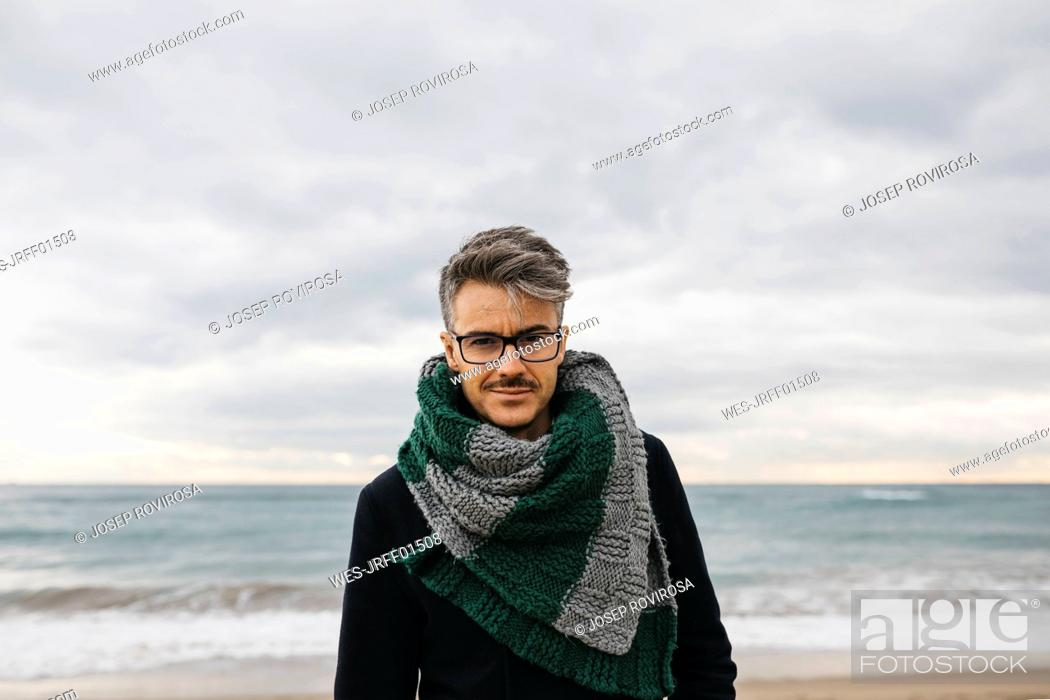 Photo de stock: Portrait of man on the beach wearing knitted scarf.