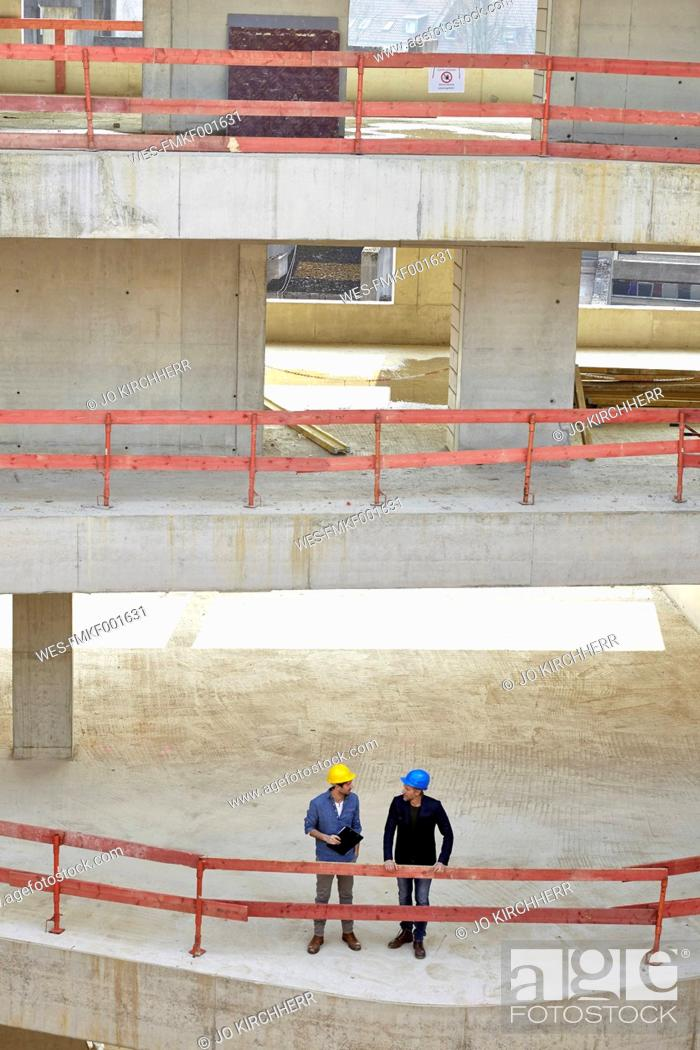 Stock Photo: Two men with hard hats talking on construction site.