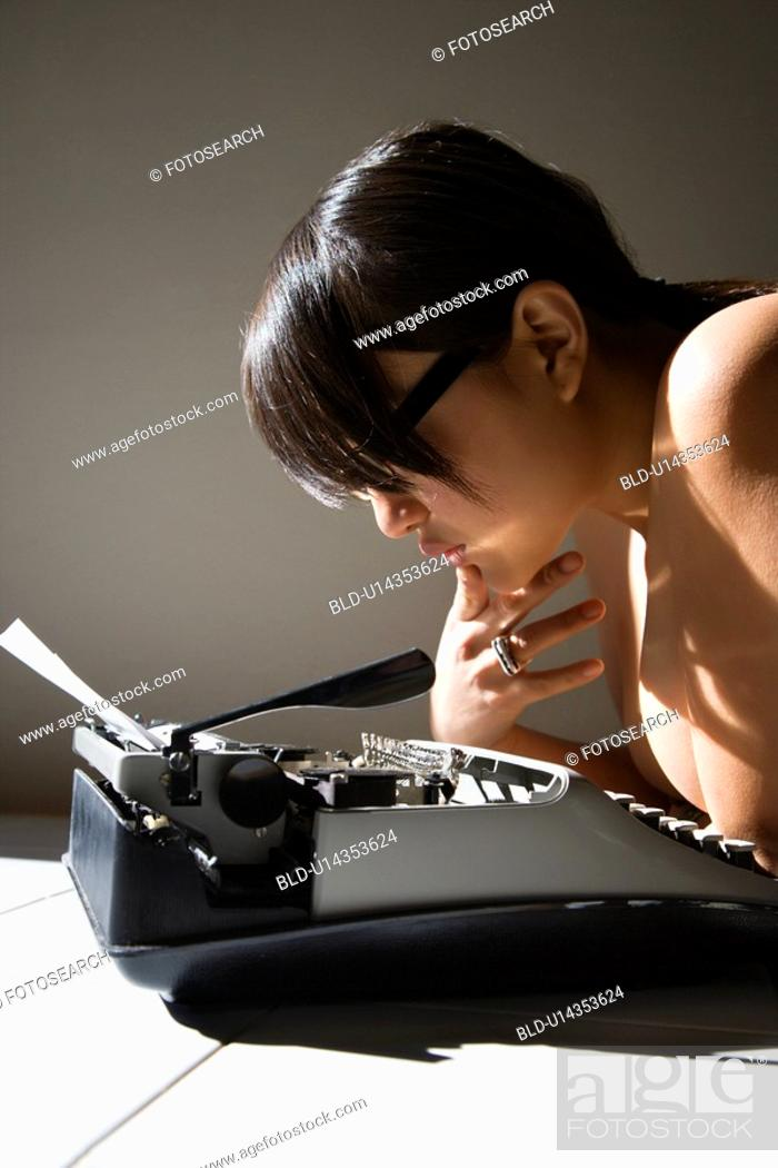 Stock Photo: Nude woman leaning on a typewriter.