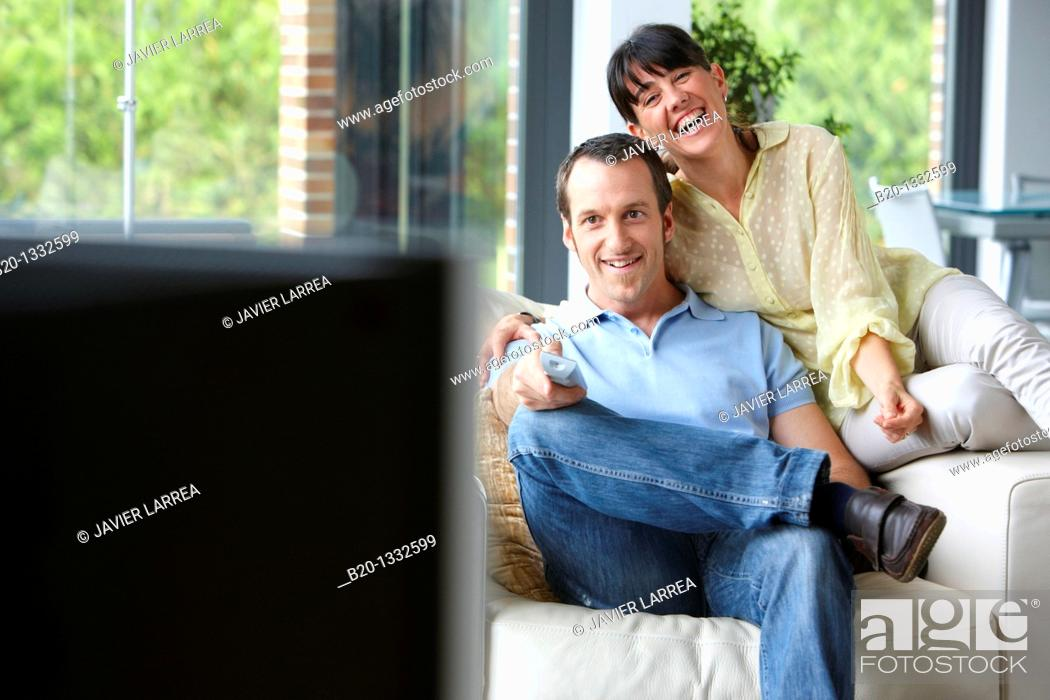 Stock Photo: Couple sitting on coach watching TV in the living room.