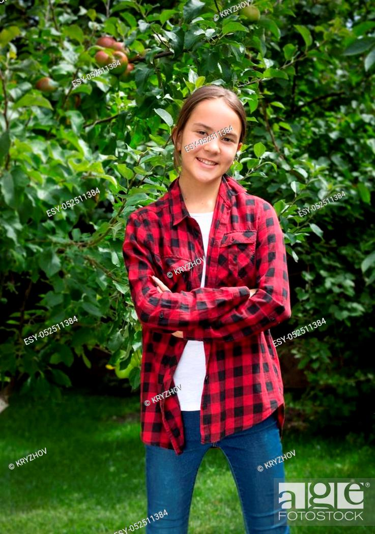 Stock Photo: Portrait of happy smiling young girl in checkered shirt posing at orchard.