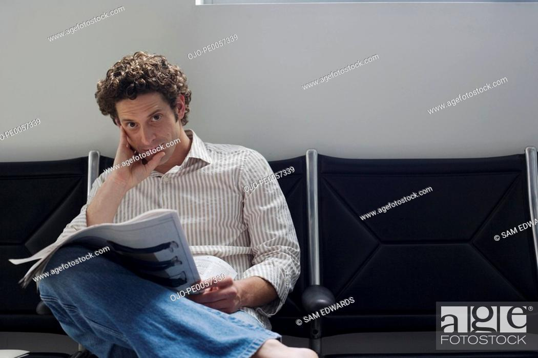 Stock Photo: Man sitting with a newspaper.