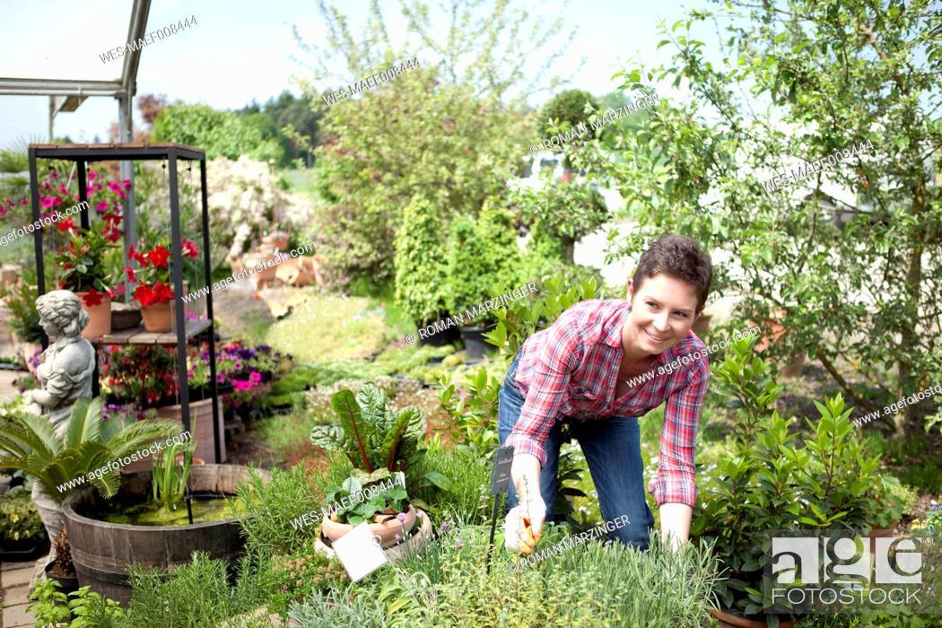 Imagen: Portrait of female gardener working in garden centre.