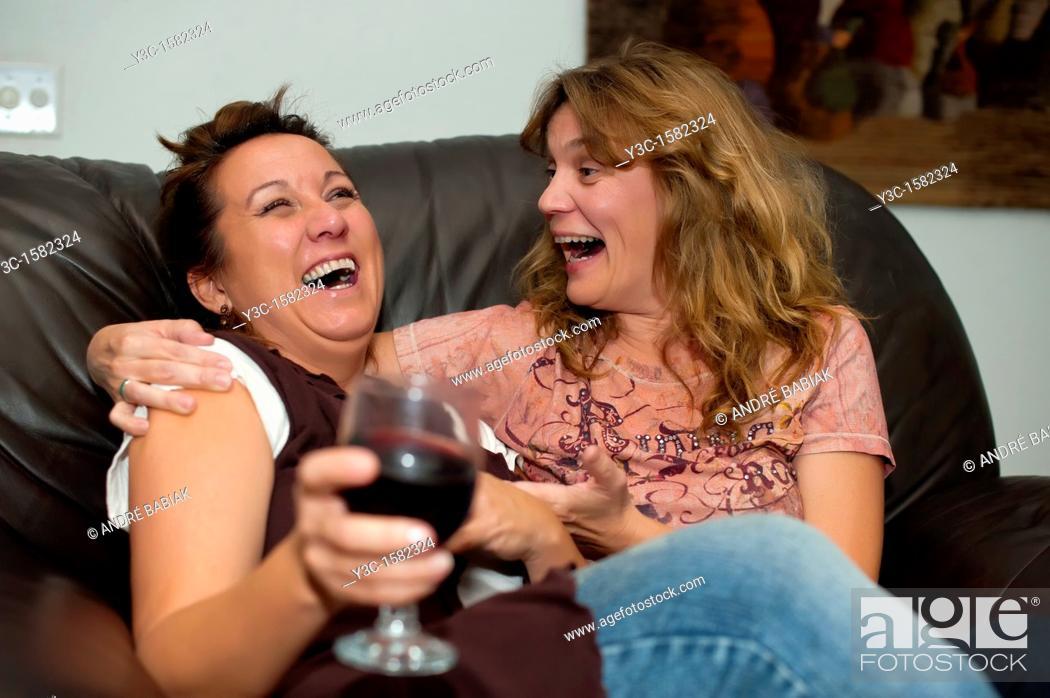 Stock Photo: Two women enjoying wine, laughing and having fun while sitting on a sofa.