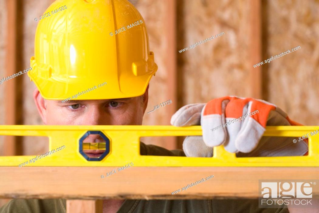 Stock Photo: Builder in hardhat using spirit level, close-up.