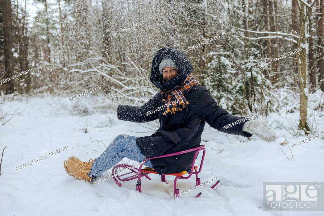 Stock Photo: Smiling woman sitting on sledge throwing snow into the air in winter forest.