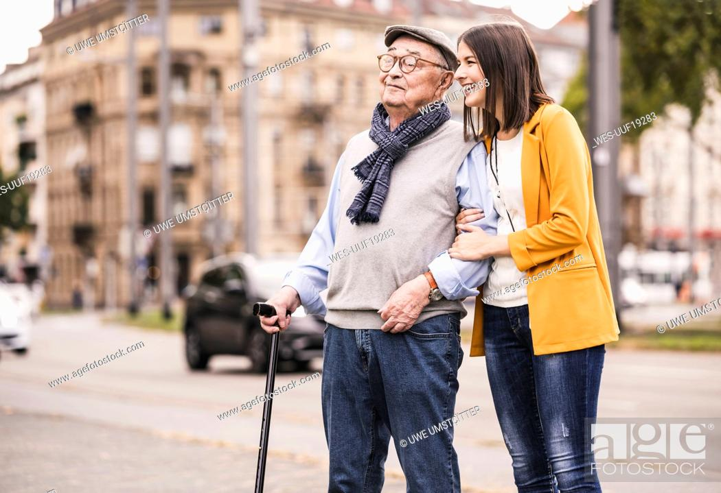 Stock Photo: Adult granddaughter assisting her grandfather strolling with walking stick.
