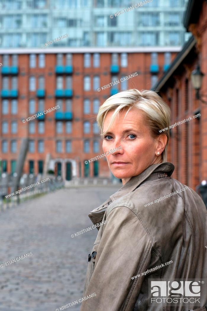Stock Photo: Blond haired executive woman, turning her head and looking back over her shoulder, seen from backside, with office building made of red bricks.