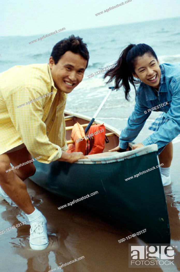 Stock Photo: Young couple pulling a canoe on the beach.