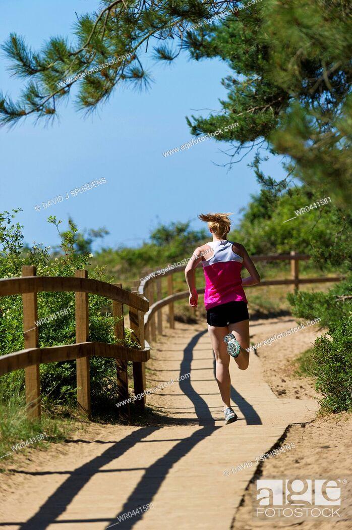 Stock Photo: A jogger running along a boardwalk through a forest to the beach.