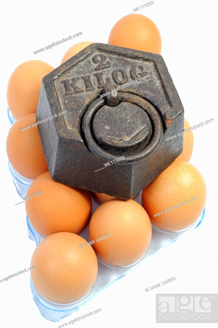 Stock Photo: Two kilos weight on eggs, white background.