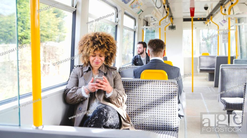 Stock Photo: Woman sitting on the train using her smartphone. There are two other passengers out of focus in the background.