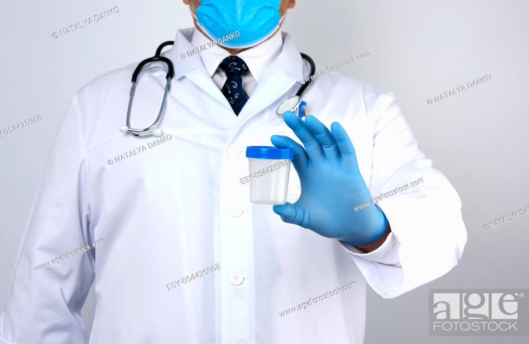 Stock Photo: male doctor in a white coat and tie stands and holds a empty plastic container for urine specimen, wearing blue sterile medical gloves.