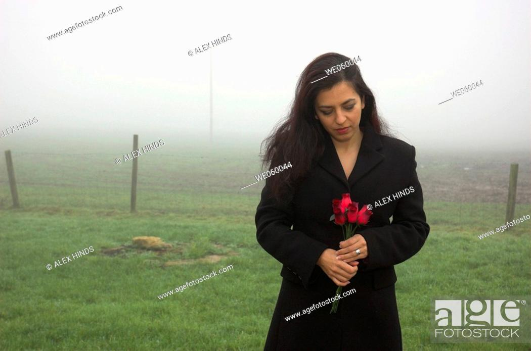 Stock Photo: Young woman standing with roses on a cold misty winter morning.