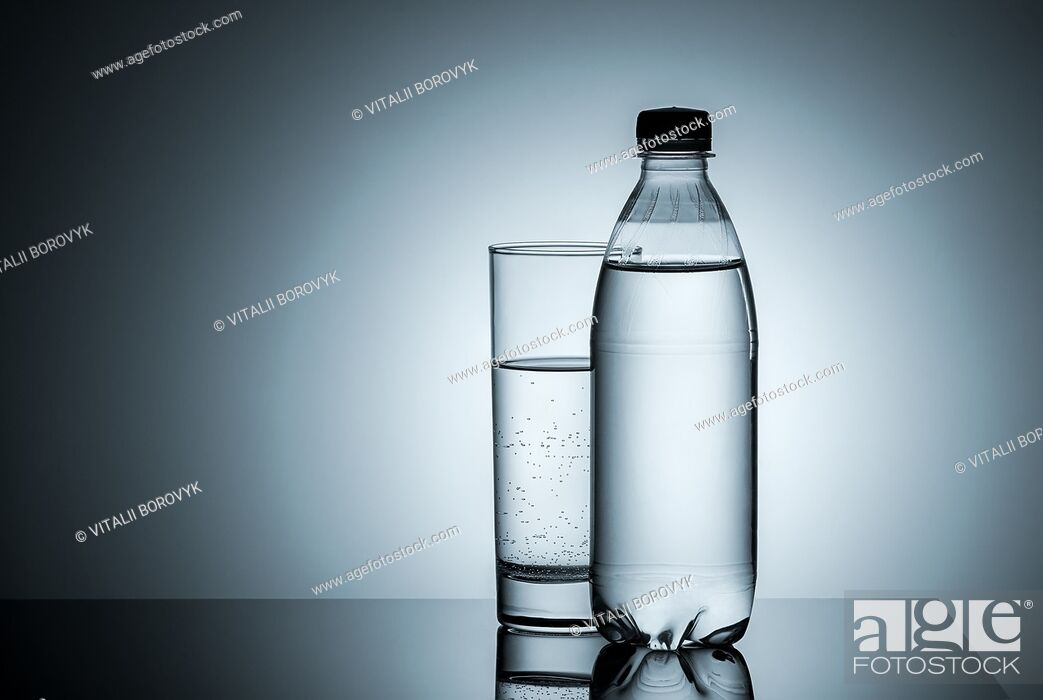 Stock Photo: Plastic bottle and glass with water. Gradient background.