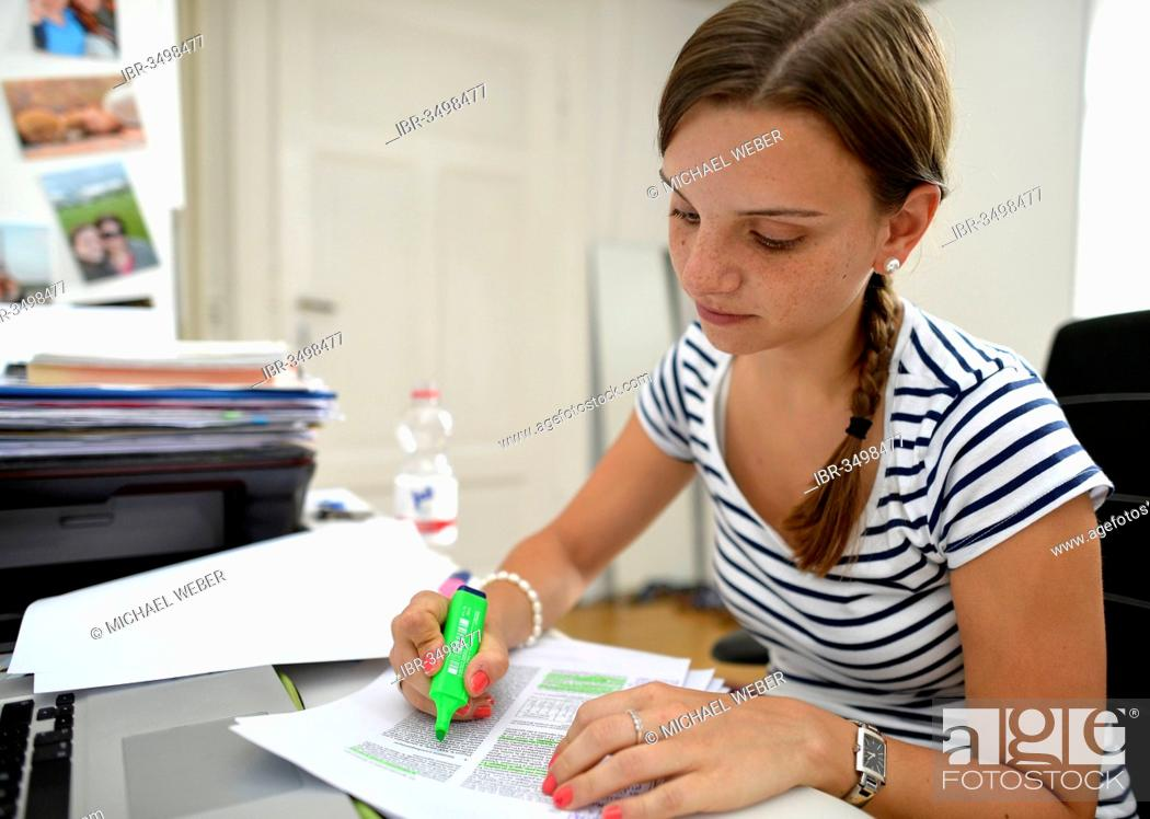 Stock Photo: Student learning in a college dorm, using a highlighter.