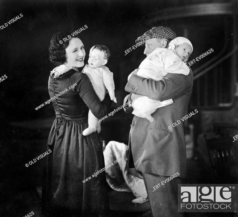 Stock Photo: Father holding baby and mother holding a doll All persons depicted are not longer living and no estate exists Supplier warranties that there will be no model.